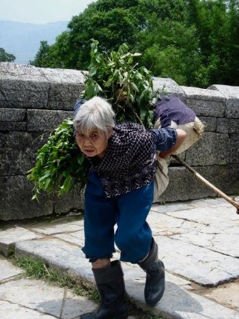 Old woman crossing the Yulong Bridge Yangshuo County Guangxi China