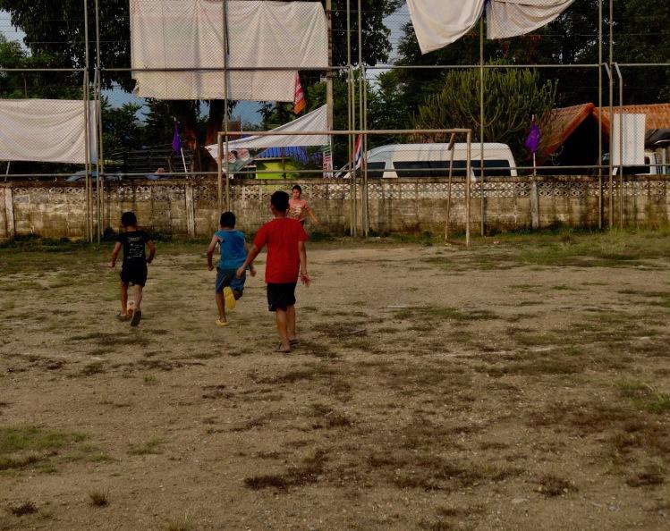 Local boys playing football Sangkhlaburi Town Market Thailand